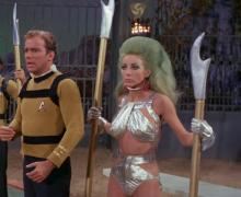 Kirk stands next to alien slave woman he later kisses.